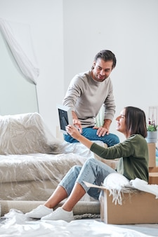 Heureuse jeune femme montrant sa photo de mari dans le cadre tout en en discutant dans le salon de leur nouvelle maison ou appartement