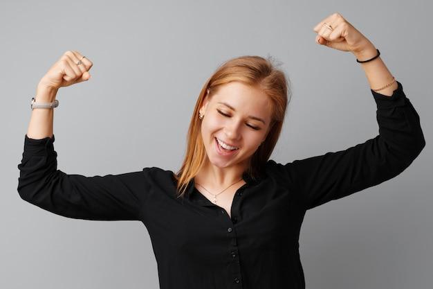 Heureuse jeune femme montrant sa victoire sur fond gris