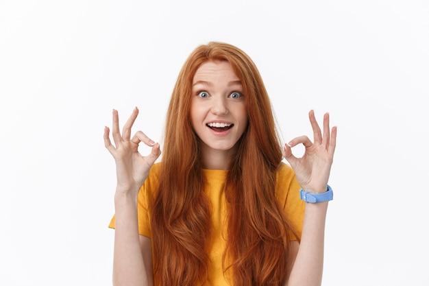 Heureuse jeune femme montrant signe ok avec les doigts un clin de œil