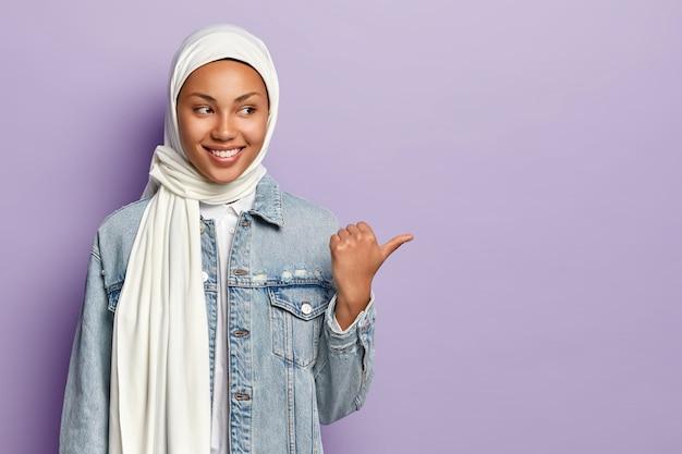 Heureuse jeune femme musulmane à l'air agréable partage une promotion intéressante pour vous, pointe du doigt