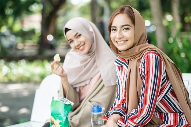 Heureuse jeune femme musulmane avec un ami profiter de leur collation tout en vous relaxant dans le parc