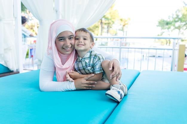 Heureuse jeune femme musulmane et petit garçon en vacances d'été