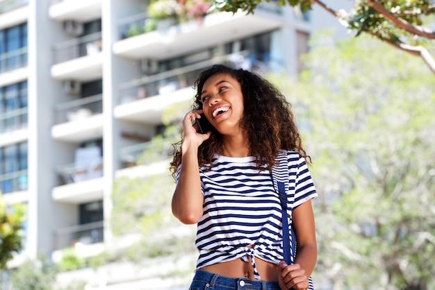 Heureuse jeune femme noire parlant au téléphone portable à l'extérieur