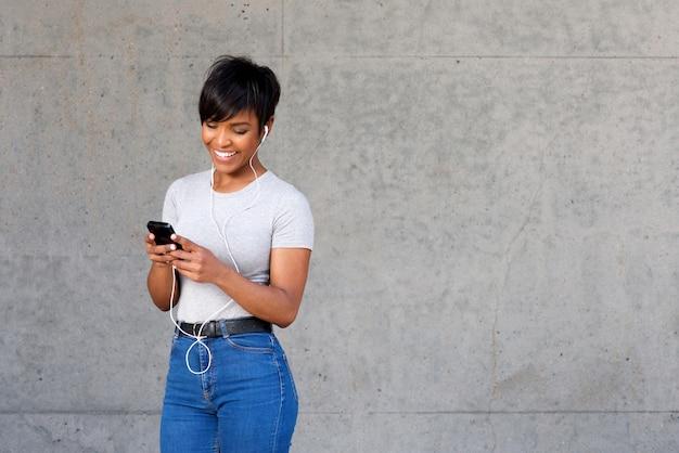 Heureuse jeune femme noire regardant un téléphone mobile et écouter de la musique