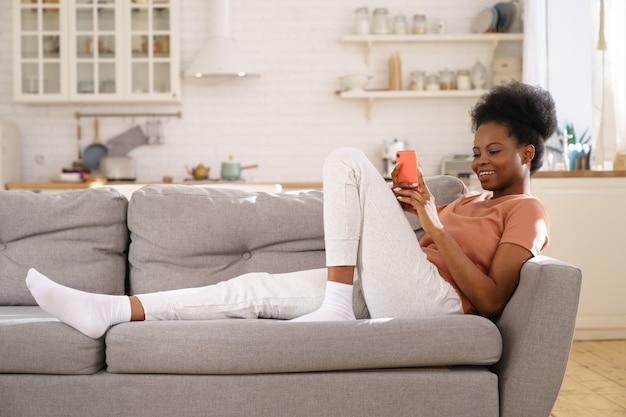 Heureuse jeune femme noire reposant sur un canapé confortable à la maison, à l'aide de smartphone, discutant dans les réseaux sociaux.