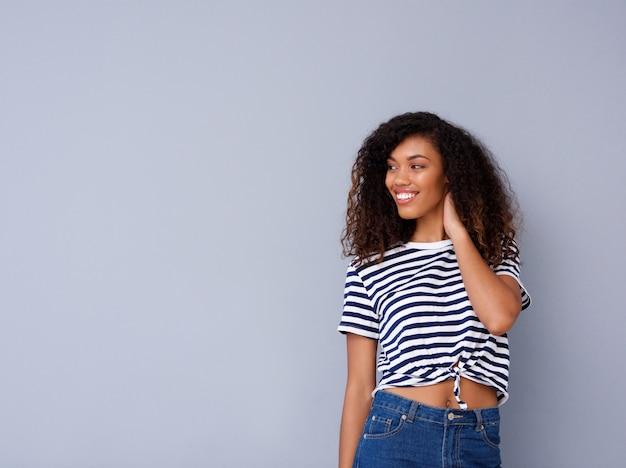 Heureuse jeune femme noire souriant en chemise rayée sur fond gris