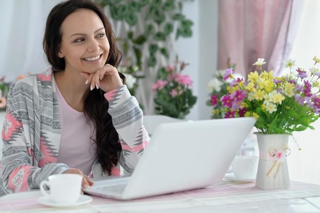 Heureuse jeune femme avec ordinateur portable à la maison
