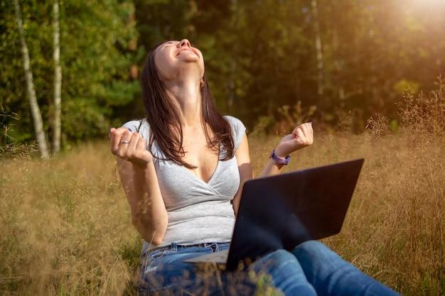 Heureuse Jeune Femme Avec Un Ordinateur Portable Sur Une Pelouse Ensoleillée, Un Pigiste Travaille Dans La Nature, étudie à Distance Photo Premium