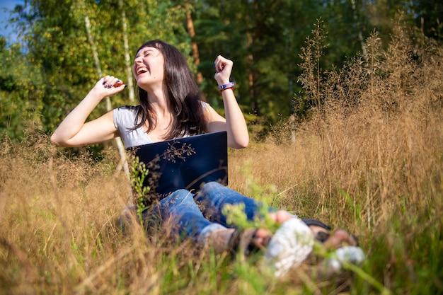 Heureuse jeune femme avec un ordinateur portable sur une pelouse ensoleillée, un pigiste travaille dans la nature, étudie à distance
