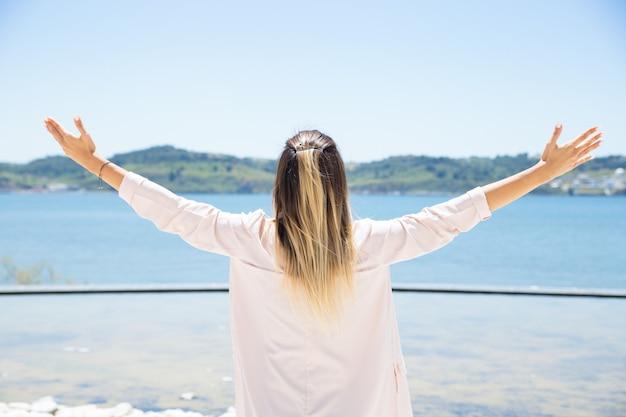 Heureuse jeune femme ouvrant les bras au paysage
