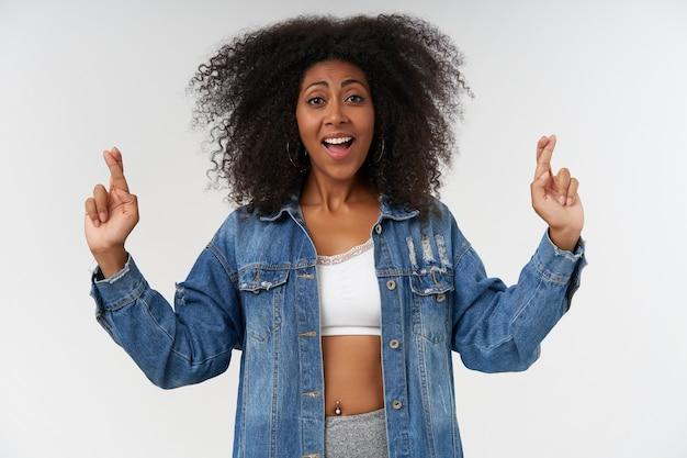 Heureuse jeune femme à la peau foncée aux cheveux bouclés croisant les index pour la bonne chance, avec un large sourire joyeux, debout sur un mur blanc en haut blanc et manteau en jean