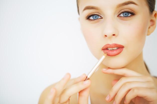 Heureuse jeune femme avec une peau parfaite, un maquillage naturel et un beau sourire