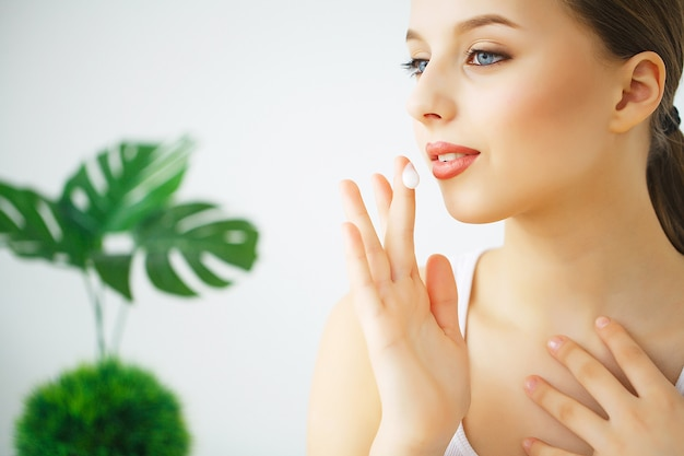 Heureuse jeune femme avec une peau parfaite, un maquillage naturel et un beau sourire.