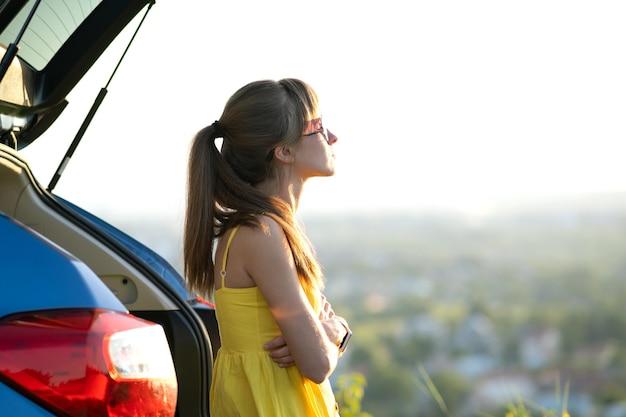 Heureuse jeune femme pilote en robe jaune profitant d'une chaude soirée d'été