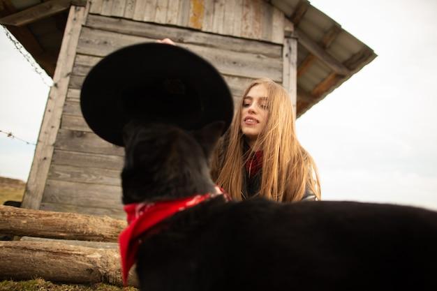 Heureuse jeune femme plaing avec son chien noir
