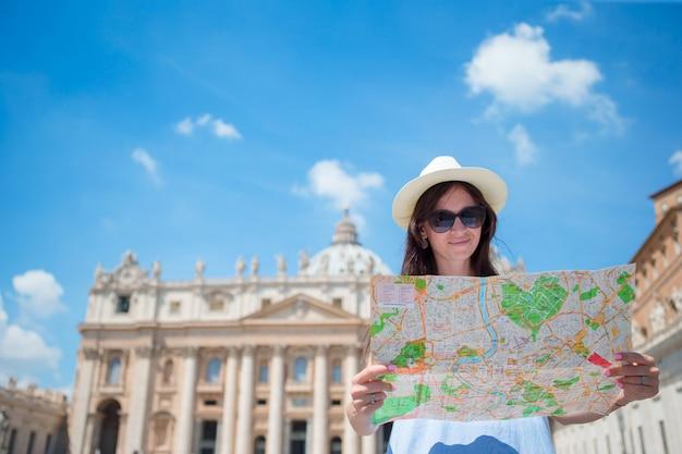 Heureuse jeune femme avec un plan de la ville