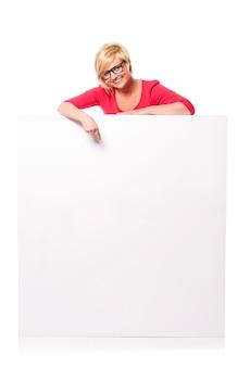 Heureuse jeune femme pointant sur le panneau d'affichage