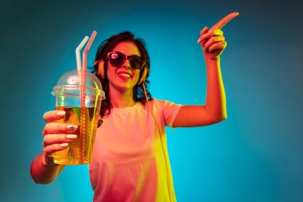 Heureuse jeune femme pointant vers le haut avec la boisson et souriant sur néon bleu à la mode