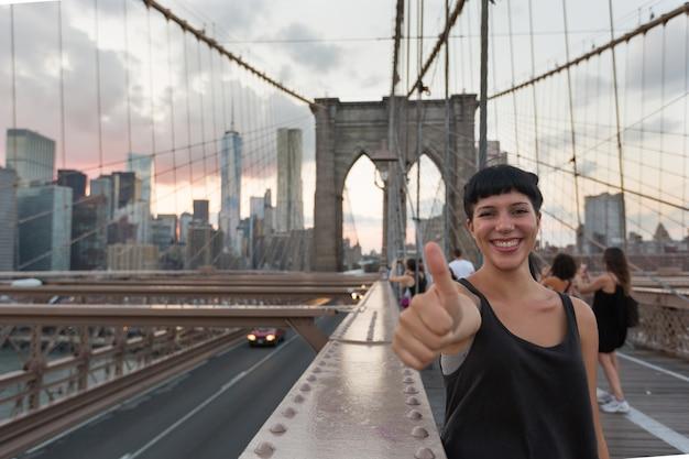 Heureuse jeune femme sur le pont de brooklyn montrant les pouces vers le haut