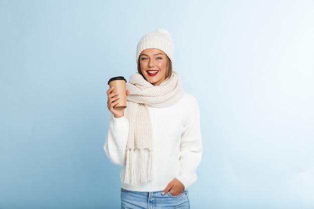 Heureuse jeune femme portant un pull et un chapeau, tenant un café à emporter