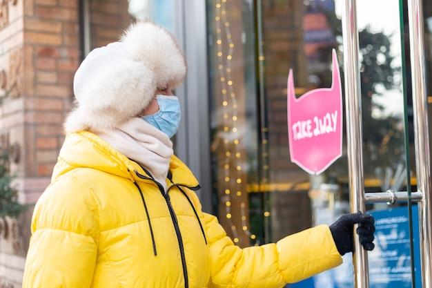 Heureuse jeune femme à la porte du restaurant par une froide journée d'hiver, lettrage, plats à emporter.