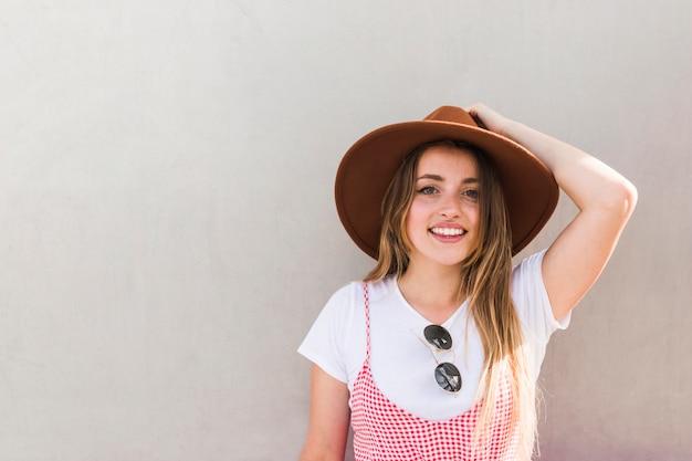 Heureuse jeune femme posant avec un chapeau