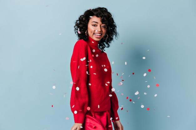 Heureuse jeune femme posant avec des confettis