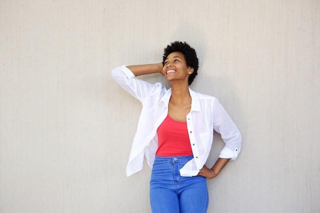 Heureuse jeune femme posant contre un mur