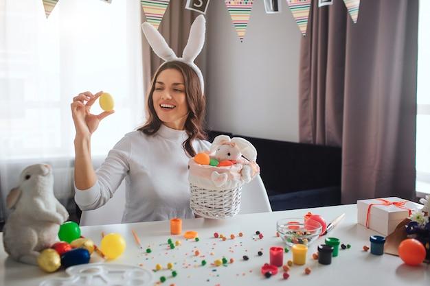Heureuse jeune femme positive préparer fo pâques seul. elle s'assoit à table dans la chambre et tient un œuf jaune. panier devant. elle sourit. décoration et bonbons sur table.