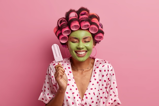 Heureuse jeune femme positive se tient les yeux fermés, tient une délicieuse crème glacée, applique des rouleaux de cheveux, fait une coiffure frisée, se soucie du teint, porte un masque de beauté vert, montre des dents blanches