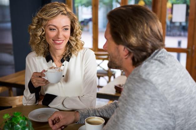 Heureuse jeune femme prenant un café tout en regardant l'homme au café
