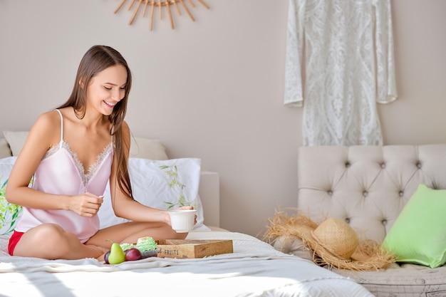 Heureuse jeune femme prenant une tasse de thé en mangeant au lit