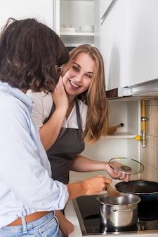Heureuse jeune femme préparant la nourriture dans la cuisine