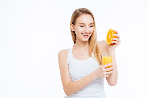 Heureuse jeune femme presse l'orange dans le jus isolé sur fond blanc