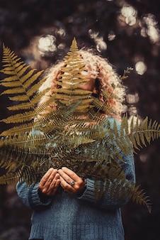 Heureuse jeune femme en pull bleu tenant des feuilles de fougère fraîches et fragiles, plante dans la forêt ou le parc. jeune femme satisfaite tenant des feuilles de plantes. la femme tient la feuille de fougère dans ses mains, couvrant une partie du visage