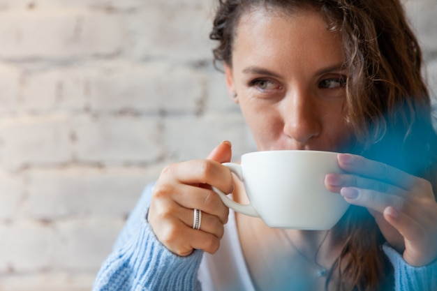 Heureuse jeune femme en pull chaud tricoté tenant avec les mains une tasse de café latte bleu chaud en bonne santé. café au lait bleu à base de grains de café frais et de thé aux pois papillon bluechai. concept de bien-être.