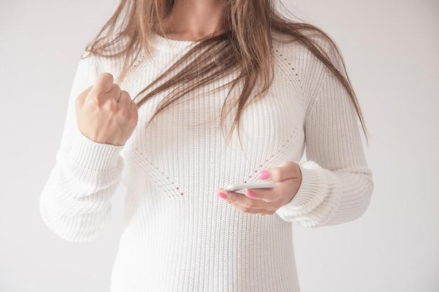 Heureuse jeune femme en pull avec téléphone intelligent, serrant les poings en geste du gagnant