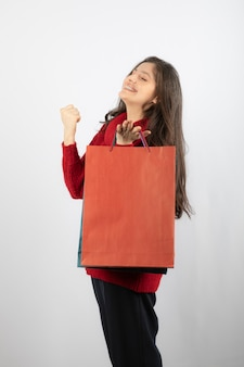 Heureuse jeune femme en pull tenant des sacs à provisions colorés.