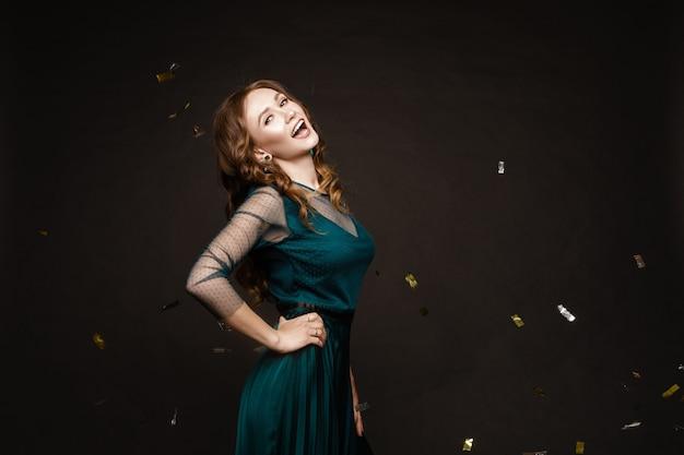 Heureuse jeune femme regardant étonnamment tout en confettis dorés tombant