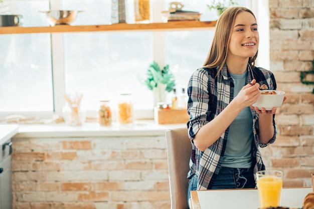 Heureuse jeune femme regardant loin et mangeant des céréales dans le bol. bannière de modèle