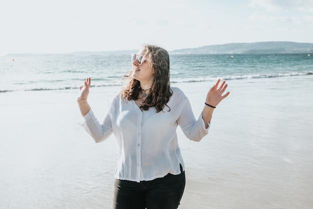 Heureuse jeune femme riant et souriant à la plage un jour d'été, profitant de vacances, concept d'amitié profitant de l'extérieur