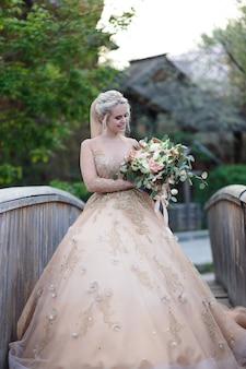 Heureuse jeune femme romantique en robe de mariée avec un bouquet de fleurs