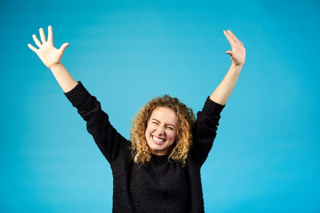 Heureuse jeune femme rousse bouclée heureuse célébrant et applaudissant un succès répandant les mains avec joie contre le bleu