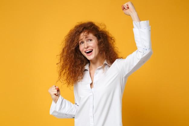 Heureuse jeune femme rousse en chemise blanche décontractée posant isolée sur un mur orange jaune