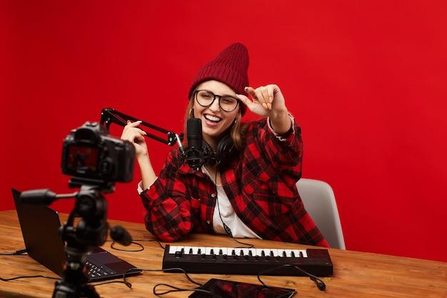 Heureuse jeune femme s'amusant assis à la table et le tournage de la vidéo pour son contenu