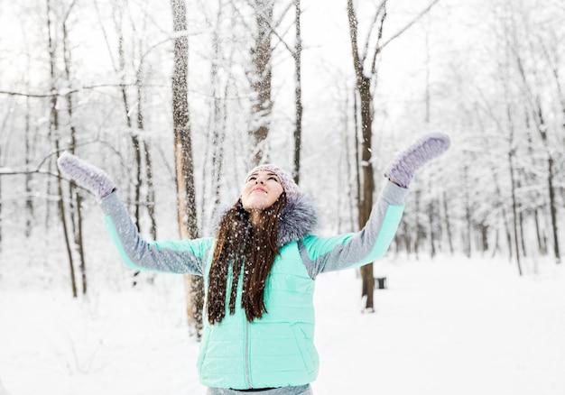 Heureuse jeune femme s'amusant dans la neige