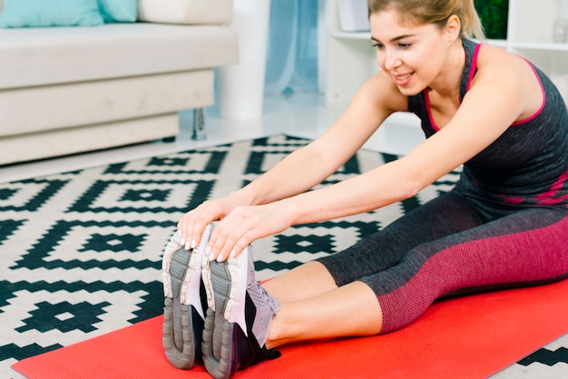 Heureuse jeune femme s'étendant ses mains tout en faisant un exercice d'échauffement
