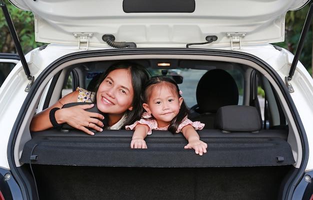 Heureuse jeune femme et sa petite fille enfant assis sur une banquette arrière