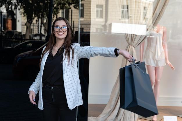 Heureuse jeune femme avec un sac à provisions noir sur fond de vitrine. étudiante après le shopping avec un sac dans ses mains.