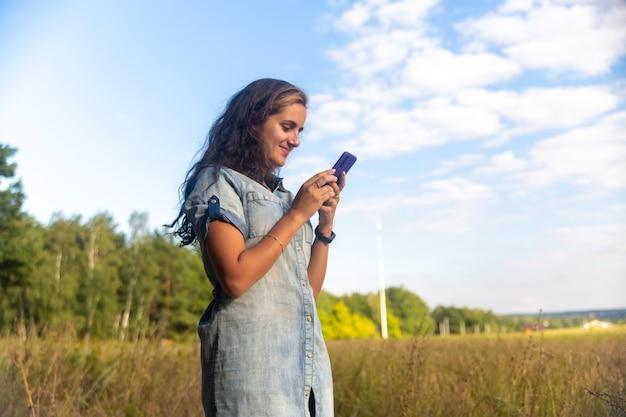 Heureuse jeune femme se penche sur le smartphone sur fond de nature aux beaux jours